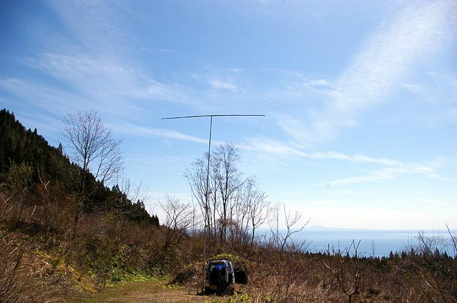 八峰町 池の台林道(F) PN90XK。右の山は男鹿本山、本山とクルマの間に寒風山、マストの向こうに鳥海山が見えるハズだが霞んで見えず。同方向の能代火力発電所はよく見えていた。