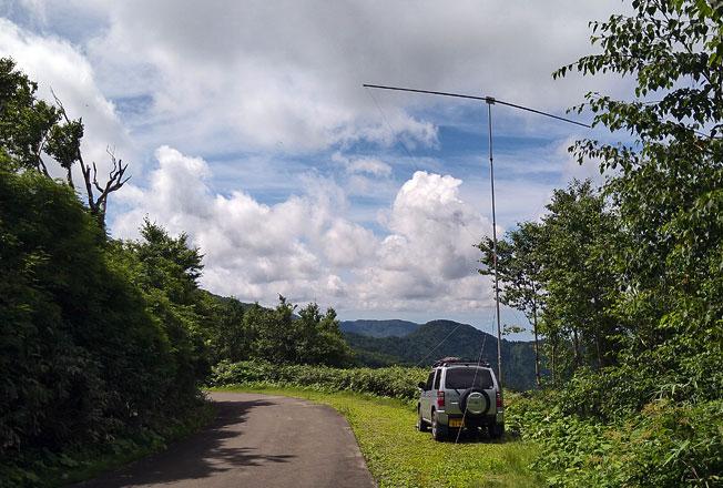 八峰町 青秋林道D 標高896m 南方向。クルマの前の山の向こうに 寒風山が見えるハズだが、かなり霞んでいる。